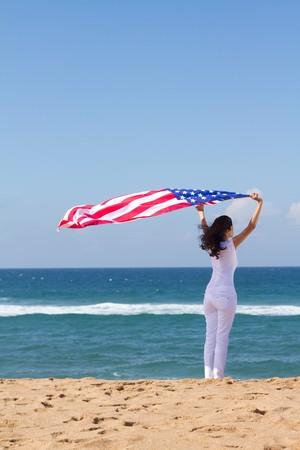 woman on beach holding american flag photo
