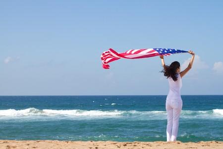 mujer sosteniendo la bandera americana en viento en playa