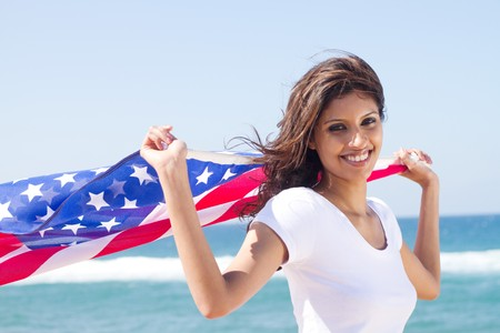 pretty american woman with flag on beach photo