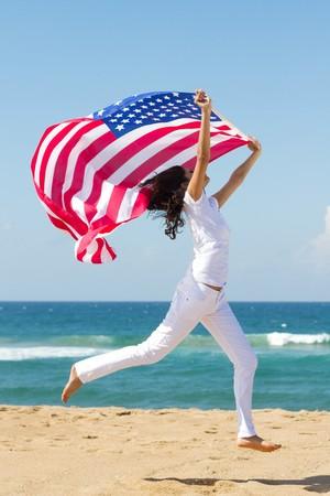 jonge vrouw met Amerikaanse vlag op strand