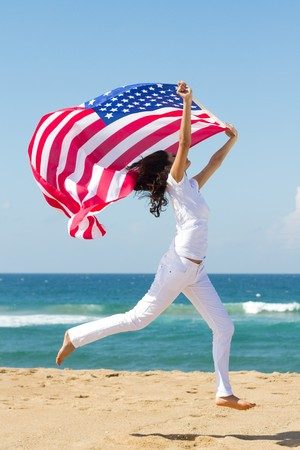 young woman holding american flag on  beach
