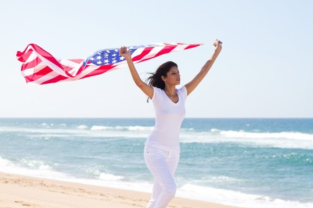 mujer que se ejecutan con la bandera de Estados Unidos en la playa  Foto de archivo