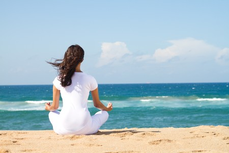 ocean view: rear view of woman meditating on beach