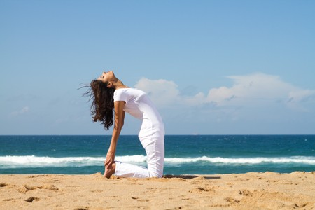 woman doing yoga poses on beach photo