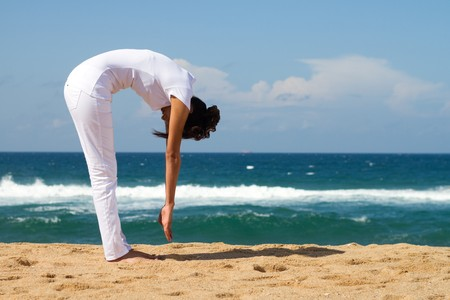 young woman doing yoga on beach photo
