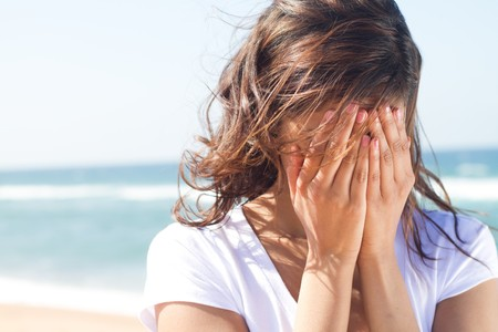 timidity: young girl crying on beach Stock Photo