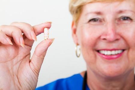 close-up of senior nurse holding pill photo