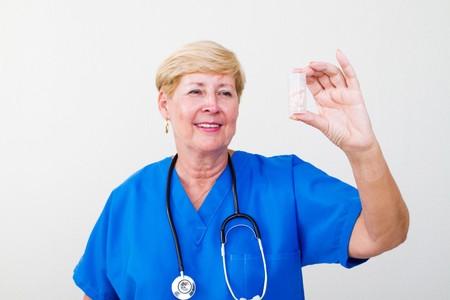 senior nurse holding bottle of pills photo