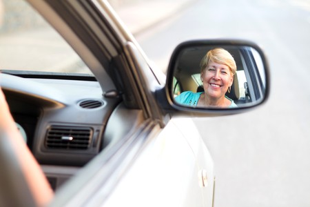 happy senior woman looking in side mirror photo