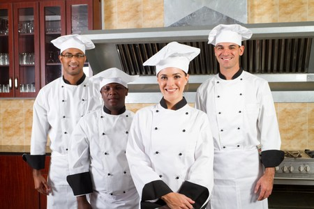 group of young happy chefs in kitchen Stock Photo