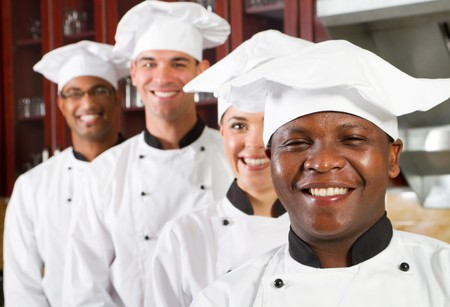 group of young happy chefs in kitchen photo