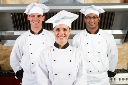 hotel kitchen: group of young happy chefs in kitchen Stock Photo