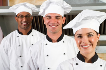 american staff: group of young happy chefs in kitchen Stock Photo