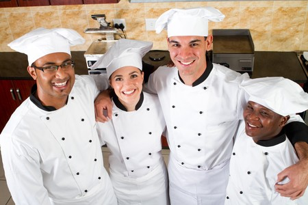 hotel staff: group of young happy chefs in kitchen Stock Photo