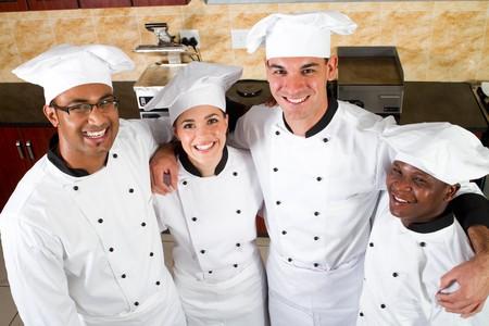 cocinas industriales: Grupo de j�venes chefs felices en cocina  Foto de archivo