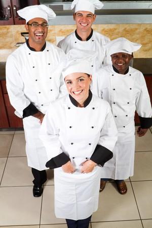 uniforme: Grupo de j�venes chefs felices en cocina  Foto de archivo