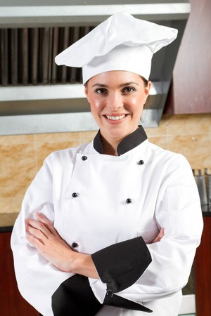 young beautiful female chef portrait in kitchen photo