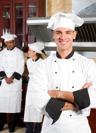 professional chefs in industrial kitchen with colleagues behind photo