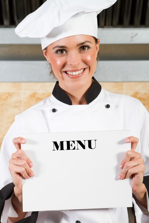 chef holding a white board or menu in kitchen photo