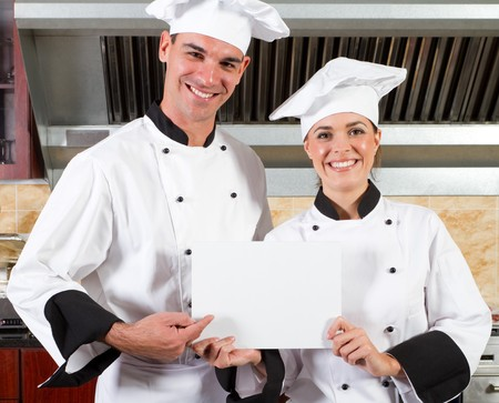 happy professional chefs holding white board in kitchen photo