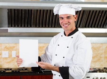 male chef holding white board in kitchen photo