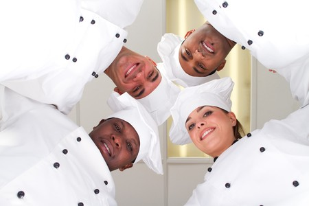 group of chefs heads together for form a team photo