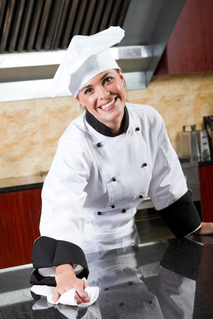 female chef cleaning commercial kitchen photo