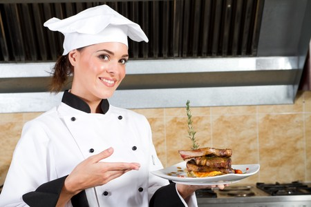 presenting: female chef presenting food in kitchen Stock Photo