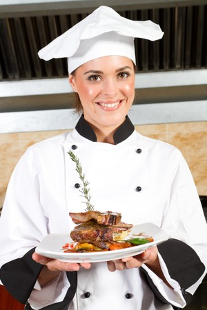 black dish: female chef presenting food in kitchen Stock Photo