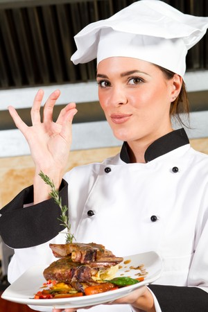 female chef presenting food in kitchen photo