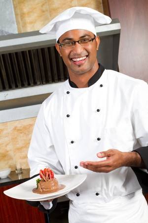 middle eastern clothing: male chef present dessert in commercial kitche