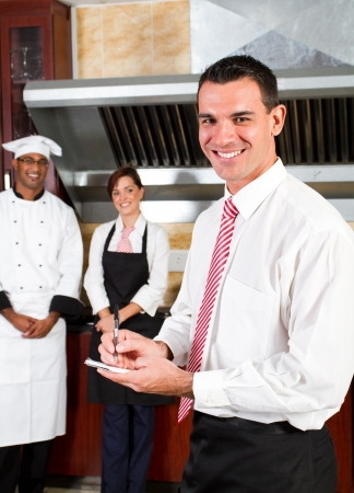 hotel worker: happy male restaurant manager and his staff in kitchen