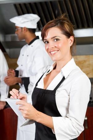 delantal: feliz mesera en el restaurante de cocina  Foto de archivo