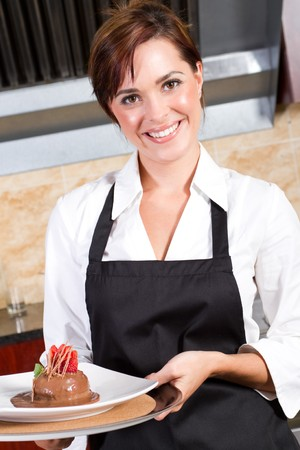 happy waitress holding plate of dessert photo
