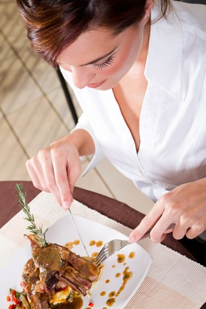 young woman eating steak in restaurant photo