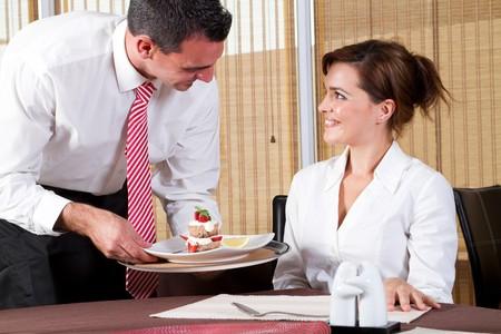 waiter brings the customer the ordered dessert photo