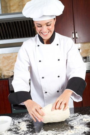 happy young female chef making dough photo