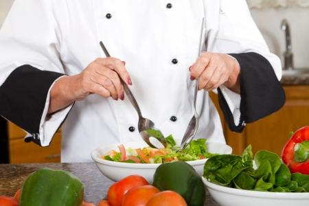meal preparation: professional female chef prepare a salad Stock Photo