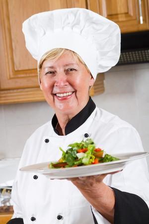 happy senior chef presenting salad photo