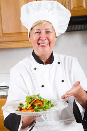 happy senior chef presenting salad photo