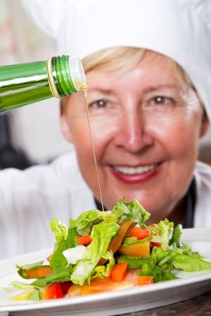senior chef pouring dressing onto salad photo