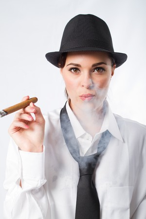 fedora: beautiful woman in mens clothing smoking cigar Stock Photo