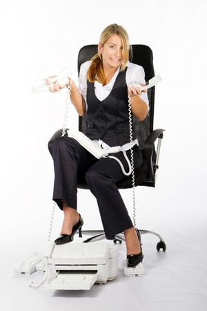 frazzled: stressed young woman holding alot of telephones in office