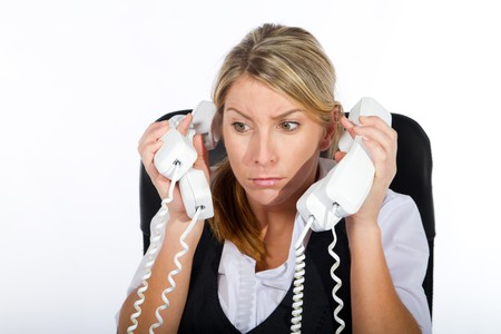 frazzled: stressed woamn answering many phones Stock Photo