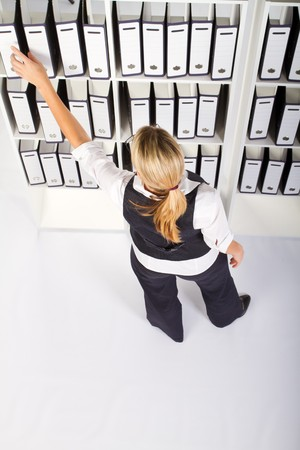 filing: businesswoman searching for files in office