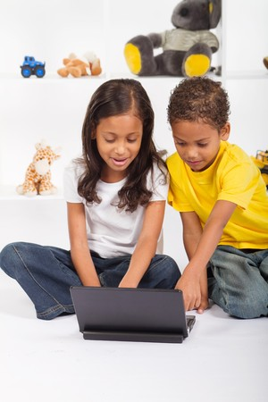 eastern siblings playing on laptop Stock Photo - 7592134