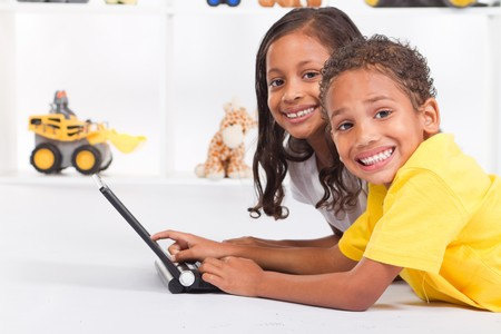 happy indian brother and sister playing laptop Stock Photo - 7592130