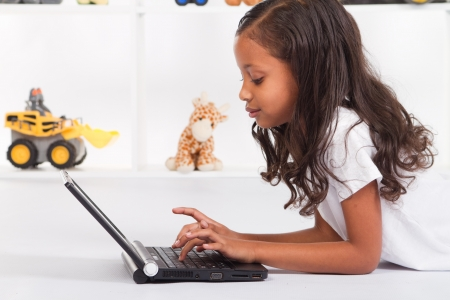biracial: african american girl playing with laptop