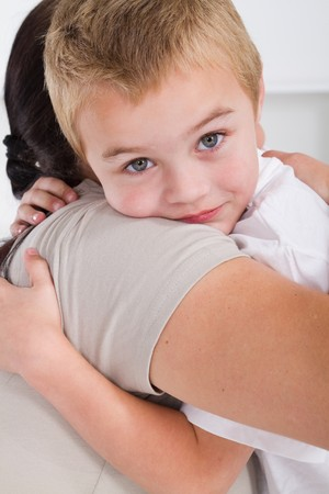 comforting: mother hugging happy young son