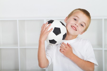 spunky: cute young boy holding soccer ball
